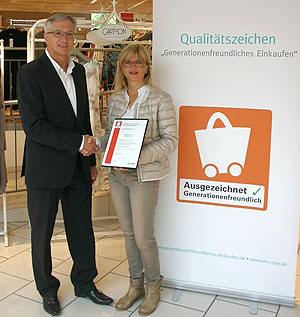 Foto: Der Geschäftsführer des Handelsverbandes Region Trier, Alfred Thielen überreicht die Urkunde an Karin Kaltenkirchen, Geschäftsführerin des Modehaus Marx.